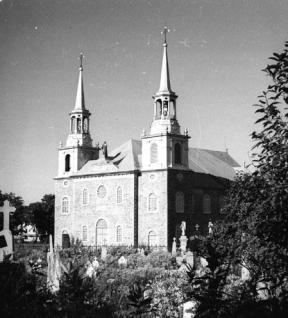 Église et ses anciens clochers en 1947, avec au premier plan, la section du cimetière consacrée aux enfants morts sans baptême (Photo: Répertoire du patrimoine culturel du Québec).